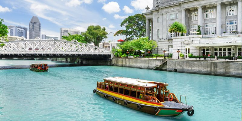 Beautiful view of traditional tourist boats sailing along the Singapore River with azure water